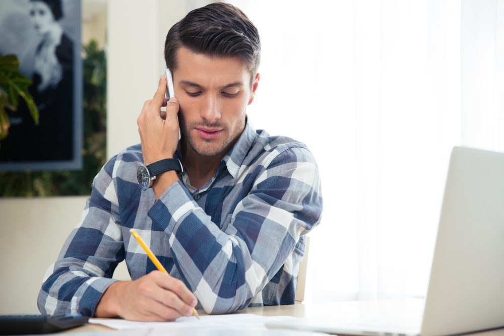 man-taking-notes-during-a-phone-call