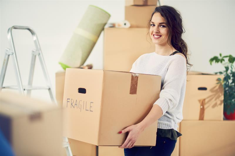 young woman carrying fragile box while moving